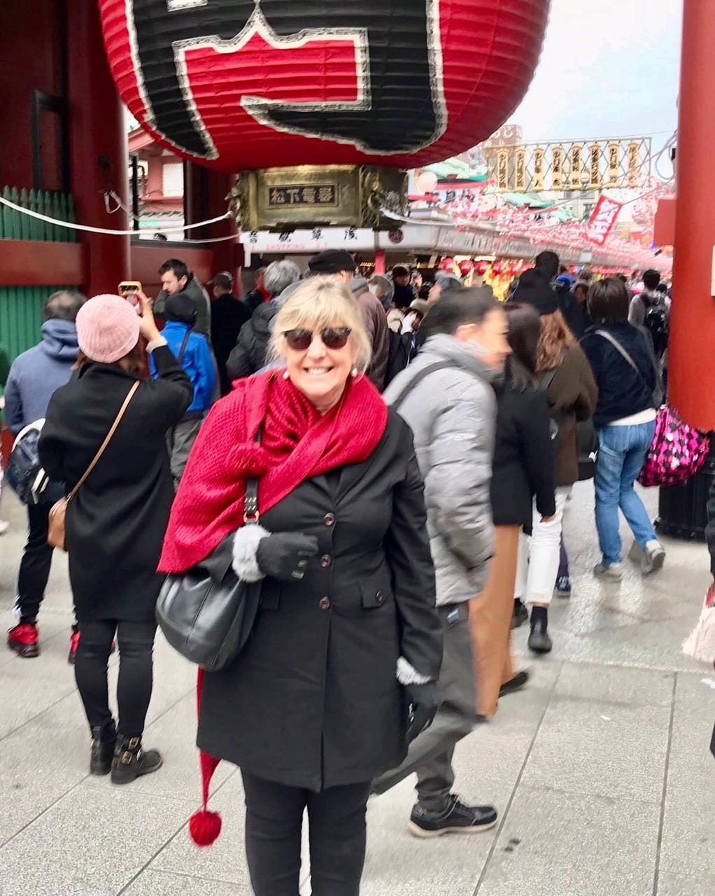 Blonde woman wearing sunglasses standing under a large red lantern in a crowd in Japan, red scarf, black coat,