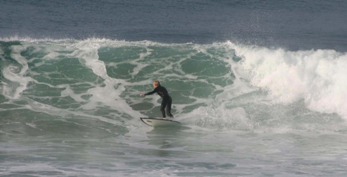 man wearing dark wetsuit surfing in the ocean